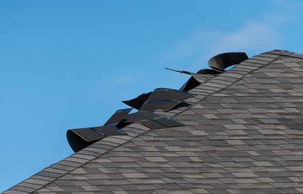 Edge of a residential roof showing significant damage