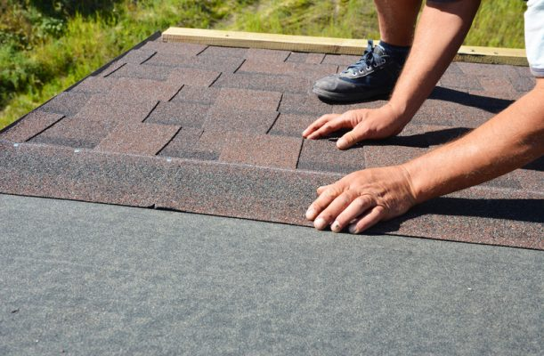 contractor installing new roof shingles by hand